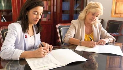 Rosa María García, vicerrectora de Estudiantes de la UGR, y Blanca Fernández, presidenta del COOOA, durante la firma del convenio.